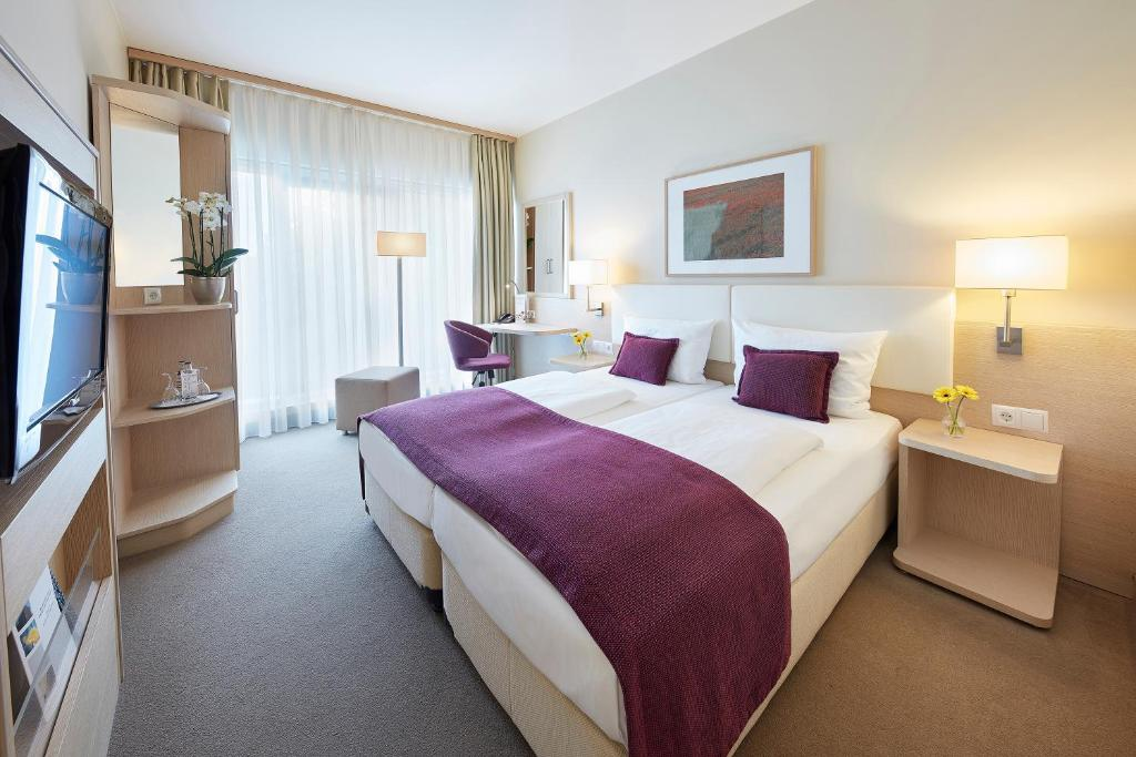 سرير أو أسرّة في غرفة في غوتيل هوتل آند ليفينغ كوبلنز