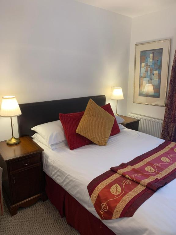 A bed or beds in a room at Jessamine House Hotel