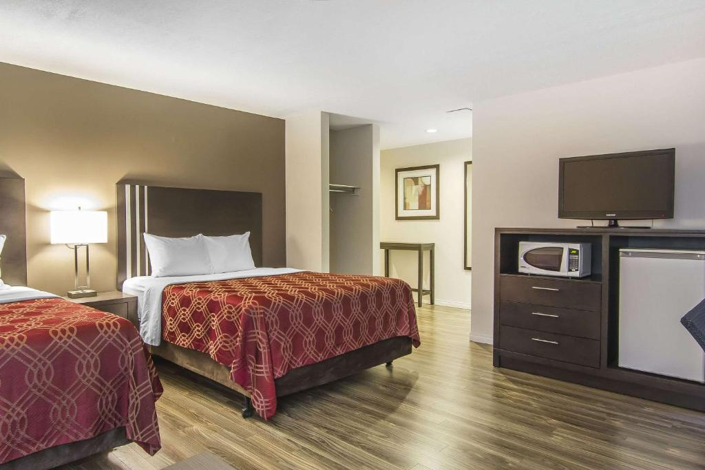 A bed or beds in a room at Econo Lodge Inn and Suites Lethbridge