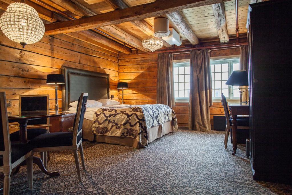 A bed or beds in a room at Det Hanseatiske Hotel