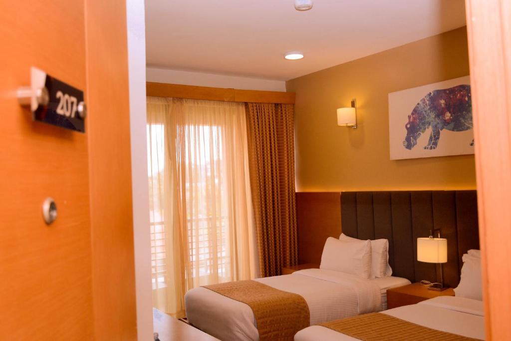 A bed or beds in a room at K Hotels Entebbe