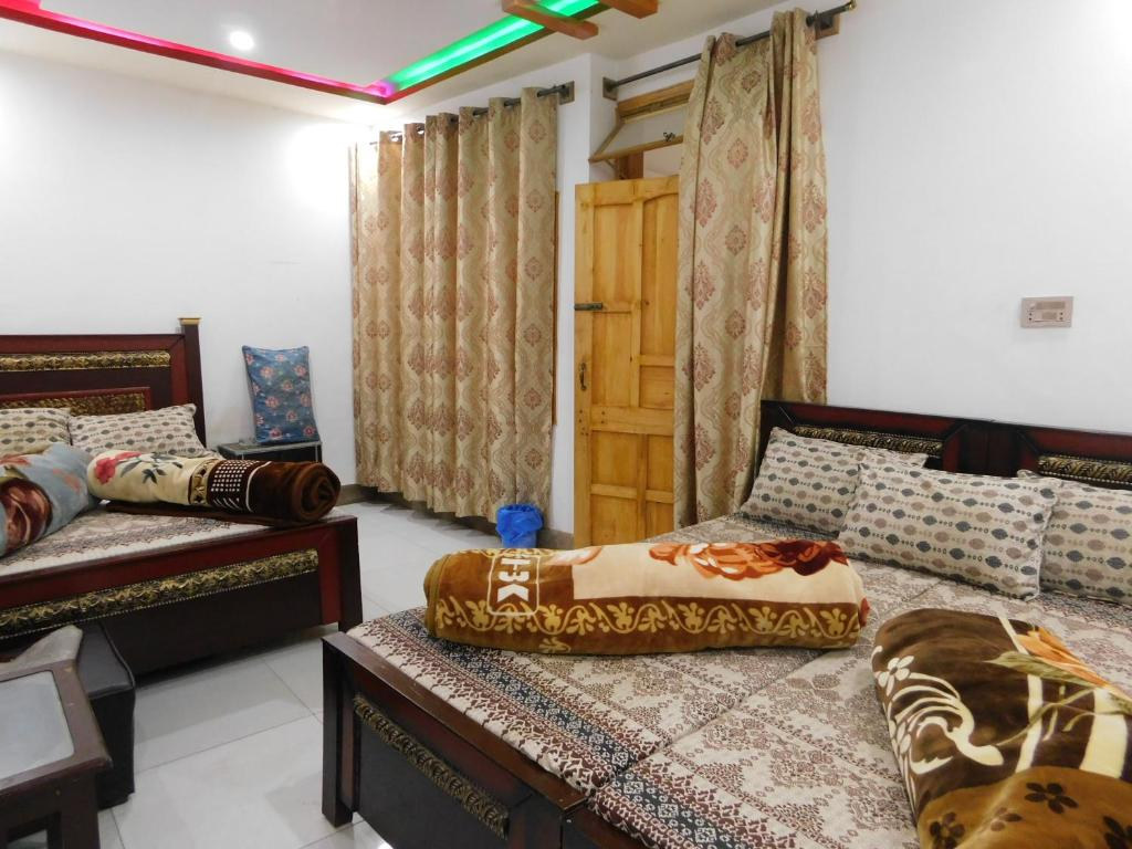 A bed or beds in a room at New Balakot Hotel