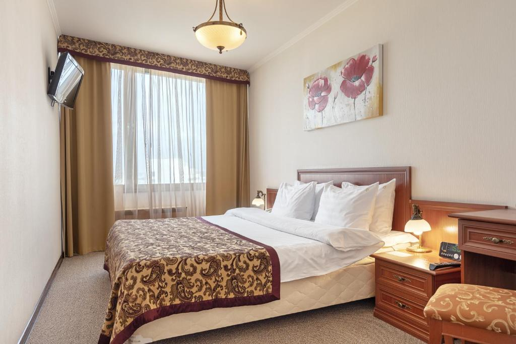 A bed or beds in a room at Astrus Hotel Moscow