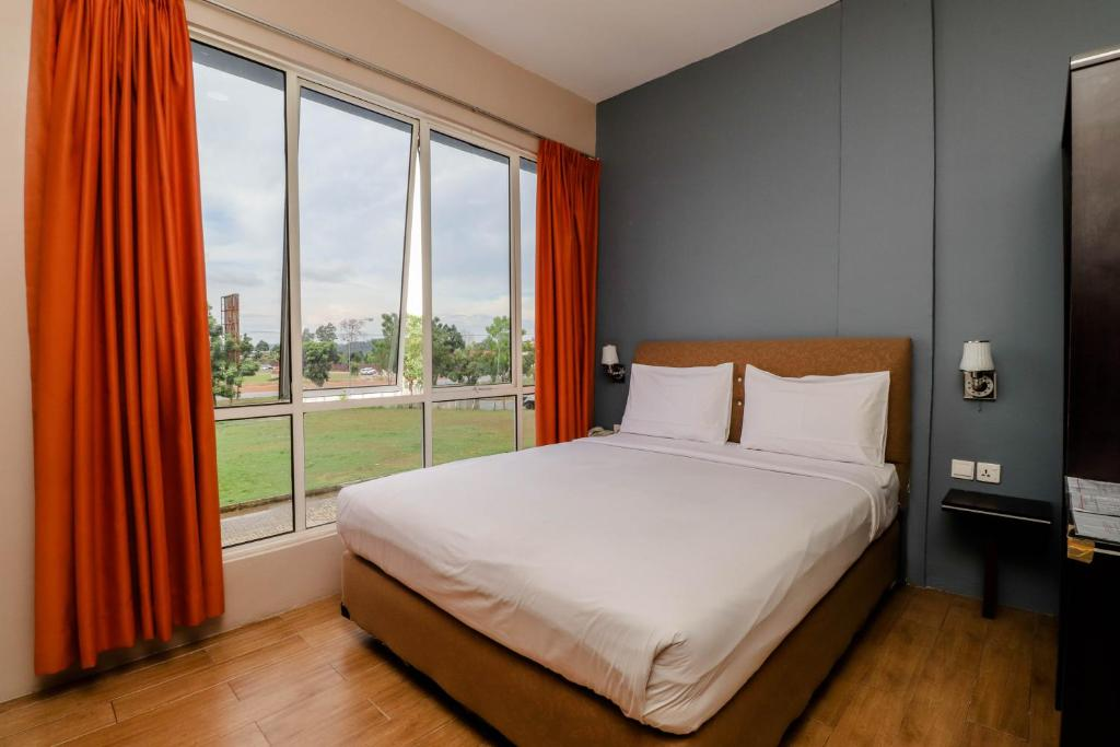 A bed or beds in a room at Blitz Hotel Batam Tanjung Uncang