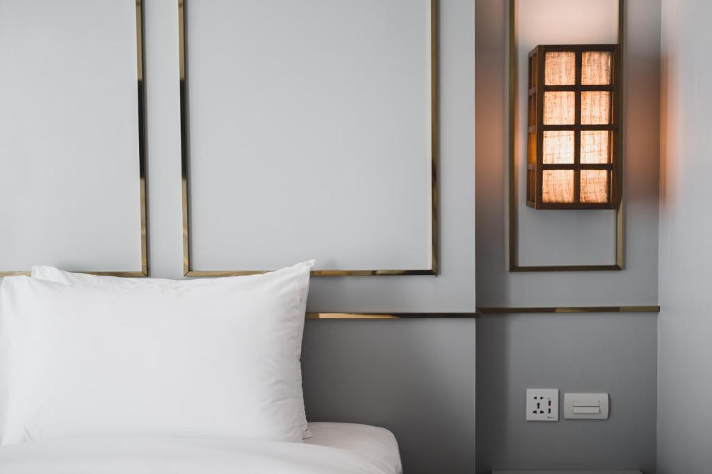 A bed or beds in a room at The Wing Boutique Hotel