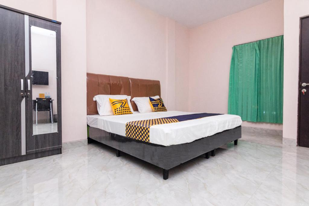A bed or beds in a room at OYO 1917 Mamora Residence