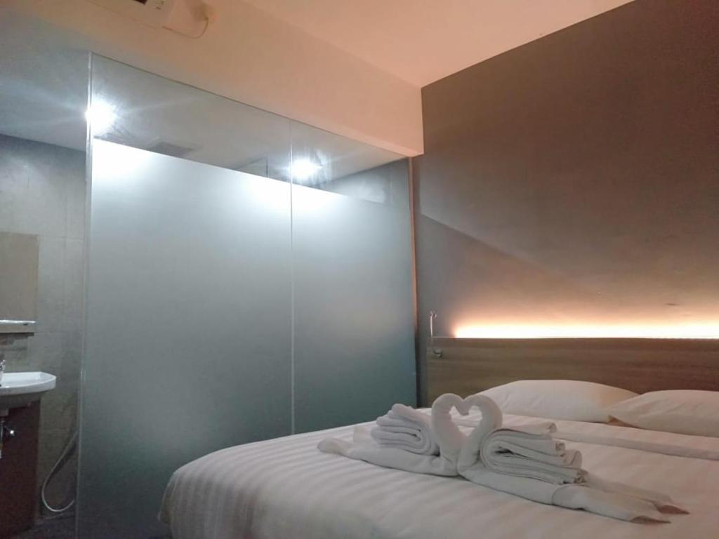 A bed or beds in a room at Hotel Marina Airport Semarang