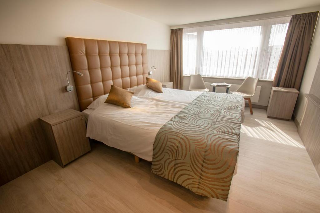 A bed or beds in a room at Hotel Atlanta Knokke