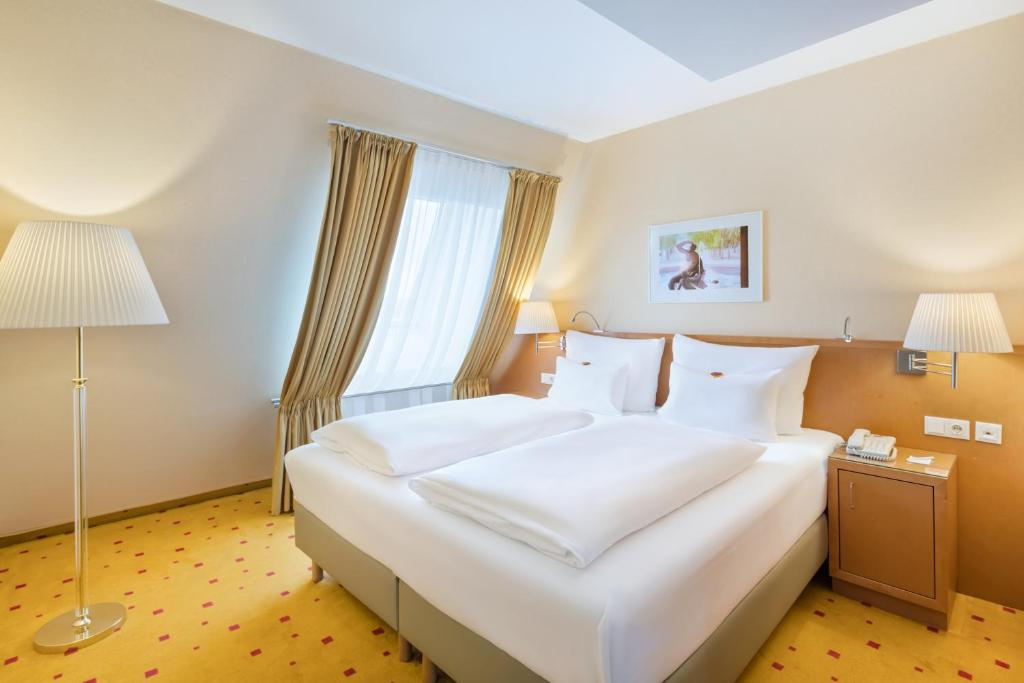 A bed or beds in a room at Austria Trend Hotel Zoo Wien