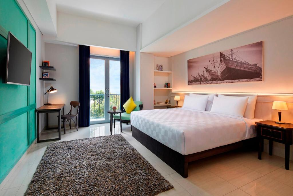 A bed or beds in a room at Jambuluwuk Thamrin Hotel