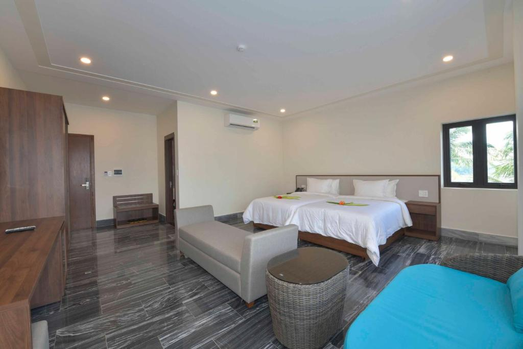 A bed or beds in a room at Cocoland River Beach Resort & Spa