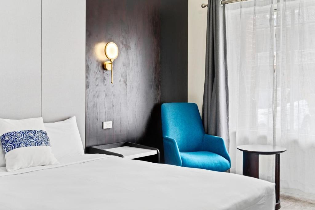 A bed or beds in a room at WM Hotel Bankstown