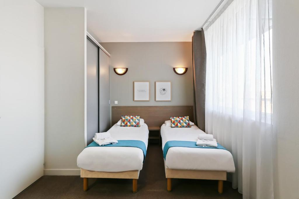 A bed or beds in a room at Appart'City Le Mans Centre