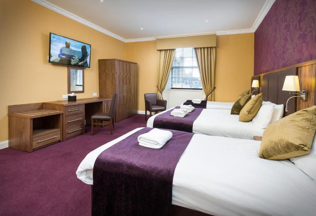 A bed or beds in a room at Albany Ballantrae Hotel