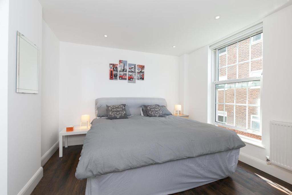 A bed or beds in a room at Modern Apartment 1mins Tube Station Sleeps 6