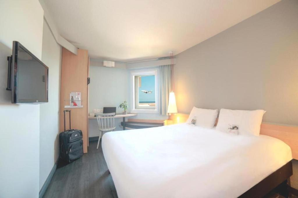 A bed or beds in a room at ibis Nice Aéroport Promenade des Anglais
