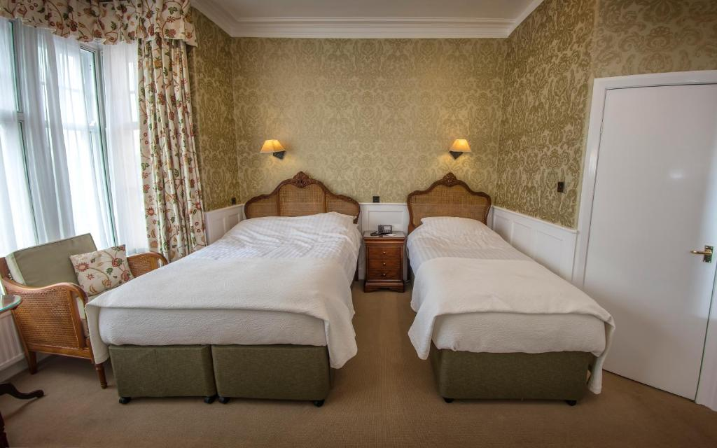 A bed or beds in a room at Dunoon Hotel
