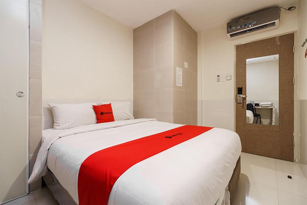 A bed or beds in a room at Permata Inn