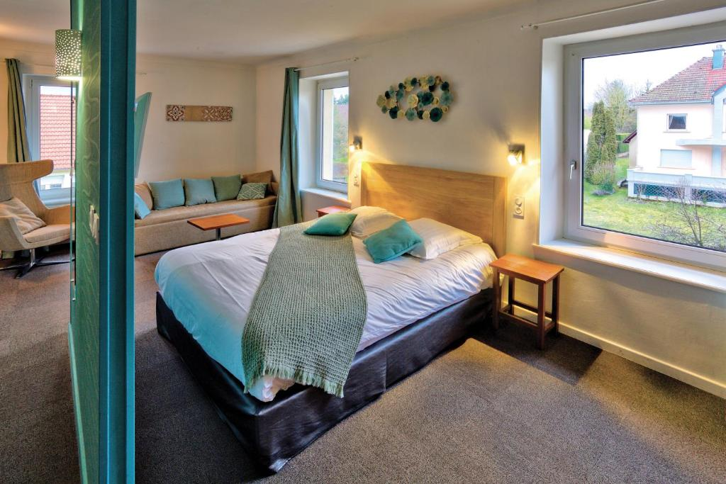 A bed or beds in a room at Logis SPA Hotel Beau Site