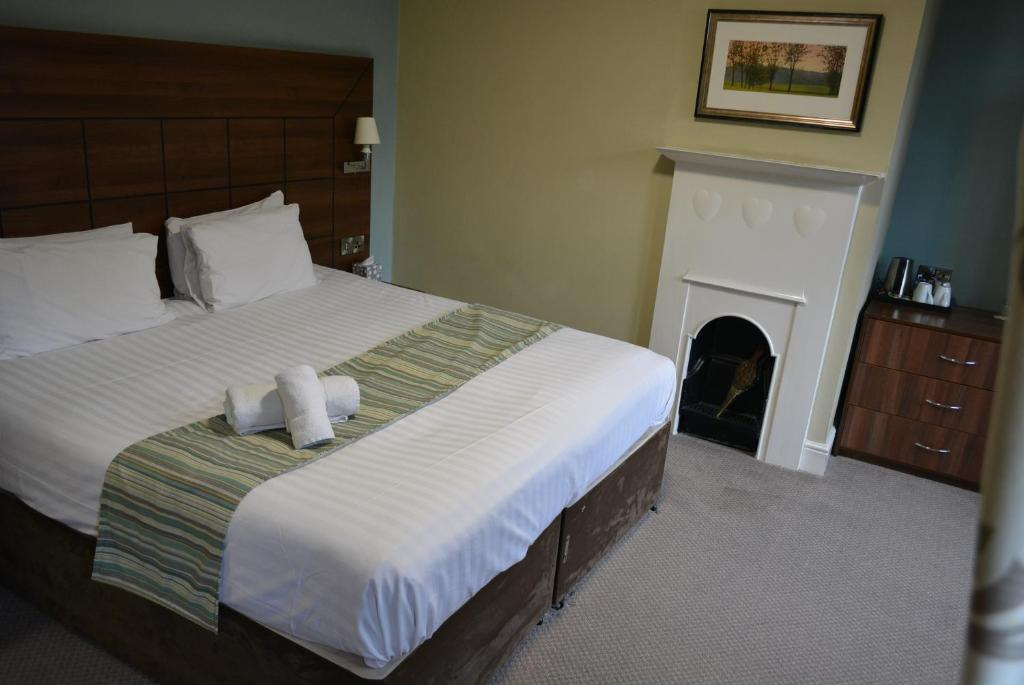 A bed or beds in a room at Quorn Grange Hotel