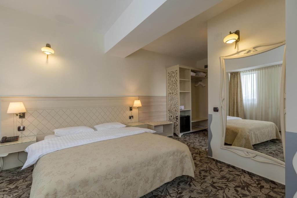 Un pat sau paturi într-o cameră la Siqua Hotel