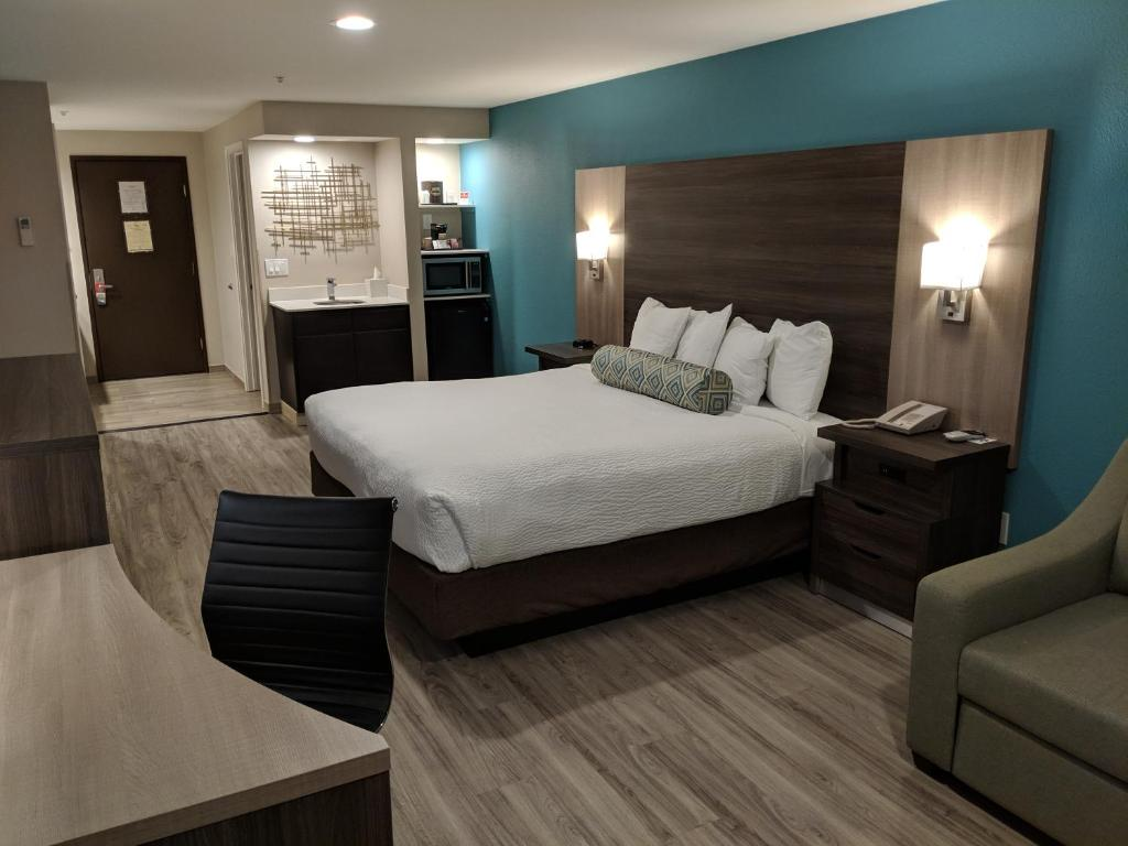 A bed or beds in a room at Yosemite Southgate Hotel & Suites