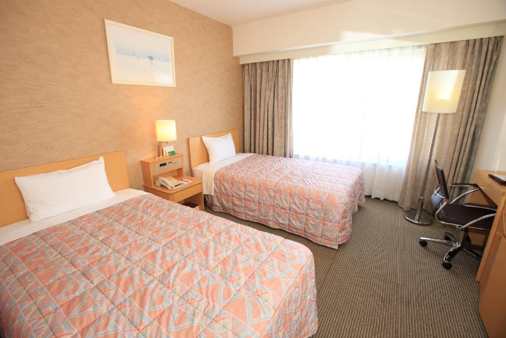 A bed or beds in a room at Bellevue Garden Hotel Kansai Airport