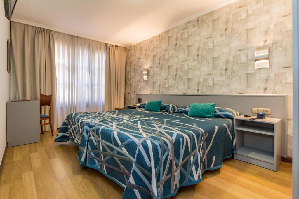 Cama o camas de una habitación en Hotel Gijon
