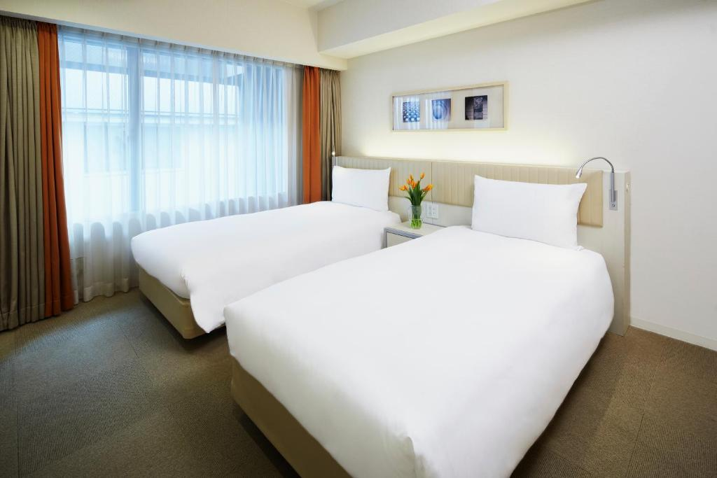 A bed or beds in a room at Citadines Kyoto Karasuma-Gojo