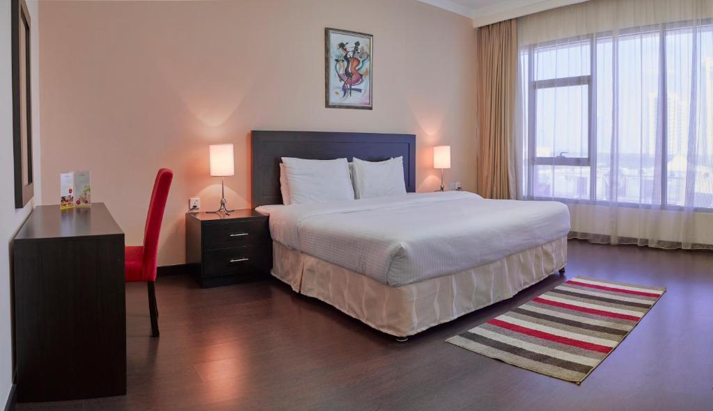 سرير أو أسرّة في غرفة في توليب ان بحرين سويتس أند ريزيدنس
