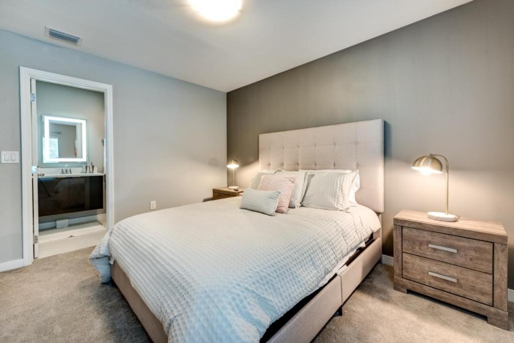 A bed or beds in a room at Enjoy Orlando With Us - Le Reve - Feature Packed Contemporary 4 Beds 3.5 Baths Townhome - 6 Miles To Disney