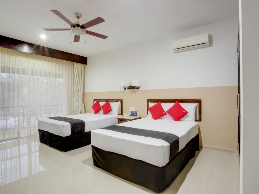 A bed or beds in a room at Capital O Koox Siglo XXI- frente al Gran Museo del Mundo Maya