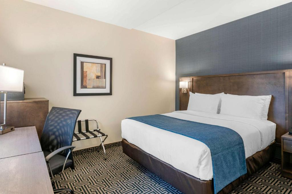 A bed or beds in a room at Quality Inn Centre-Ville