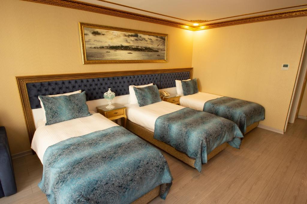 A bed or beds in a room at Empire Suite Hotel