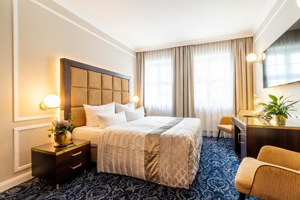 En eller flere senge i et værelse på Hotel Suitess