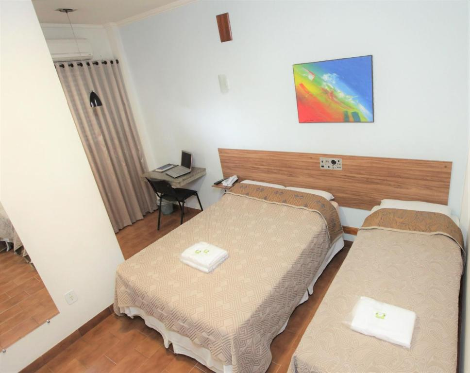 A bed or beds in a room at Hotel Pouso Novo