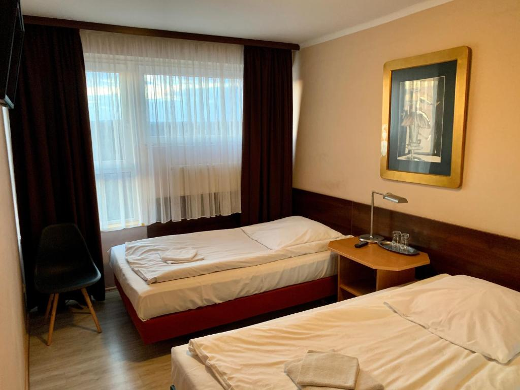 A bed or beds in a room at Gościniec Raciborski