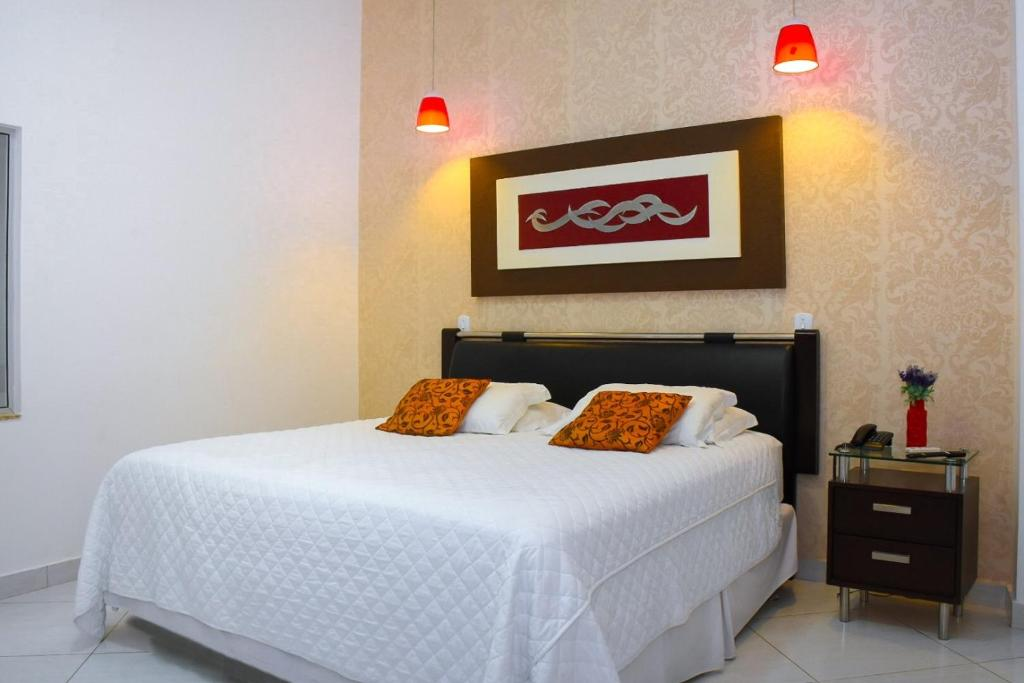 A bed or beds in a room at Pioneiro Hotel