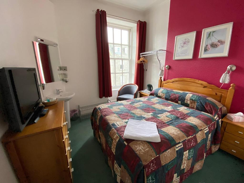 A bed or beds in a room at The Royal Crown Guest House