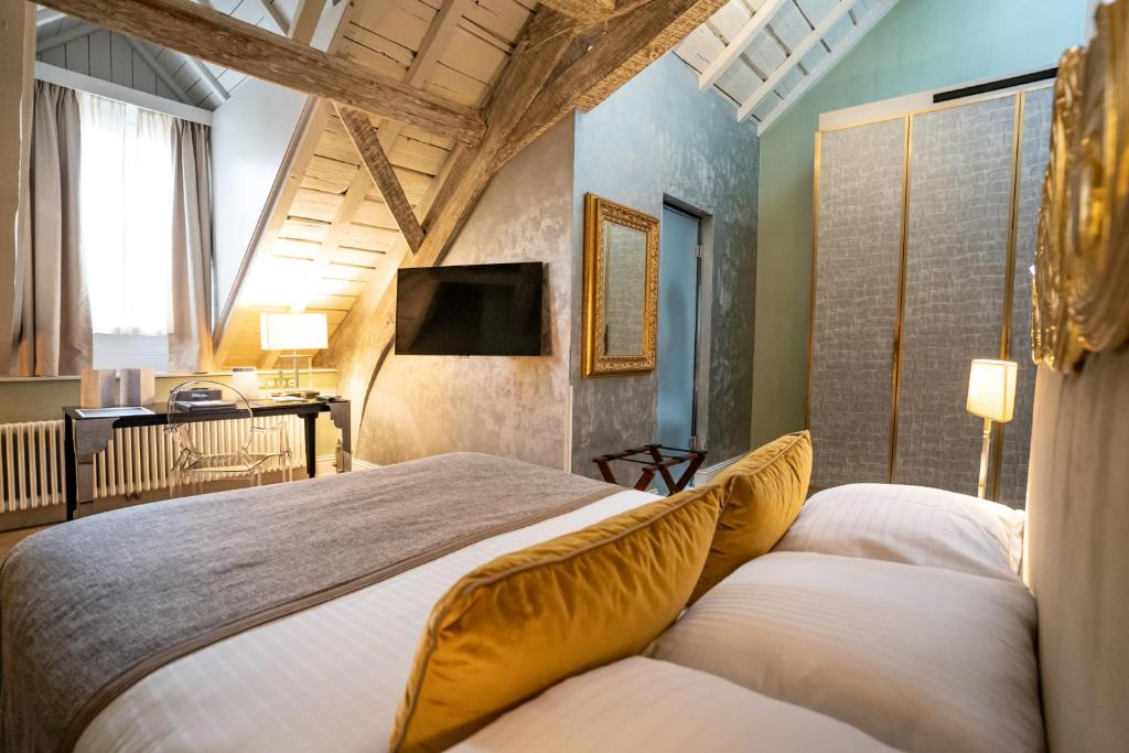 A bed or beds in a room at Hotel Le Place d'Armes