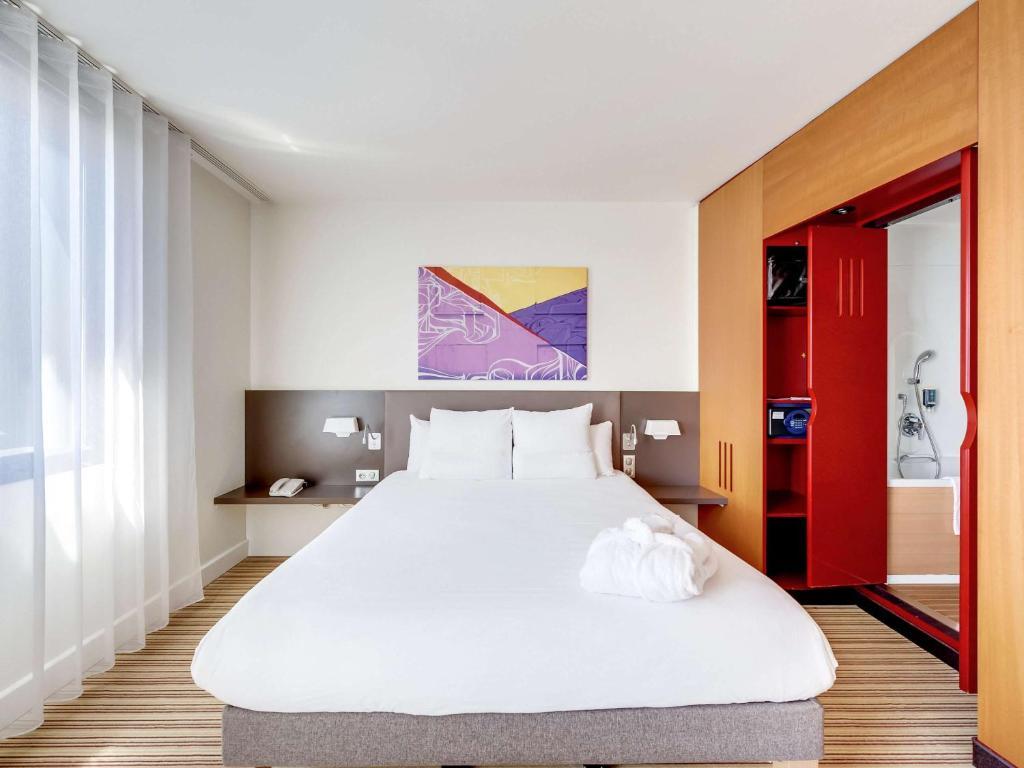 A bed or beds in a room at Novotel Suites Paris Nord 18ème