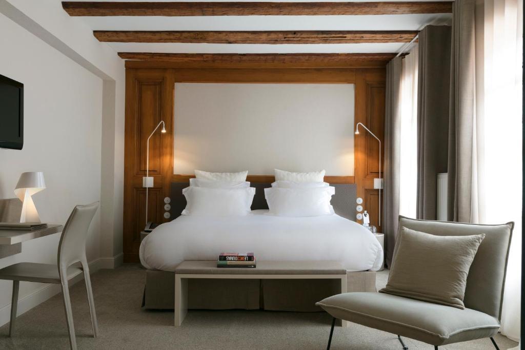 A bed or beds in a room at Relais & Châteaux La Maison Des Têtes
