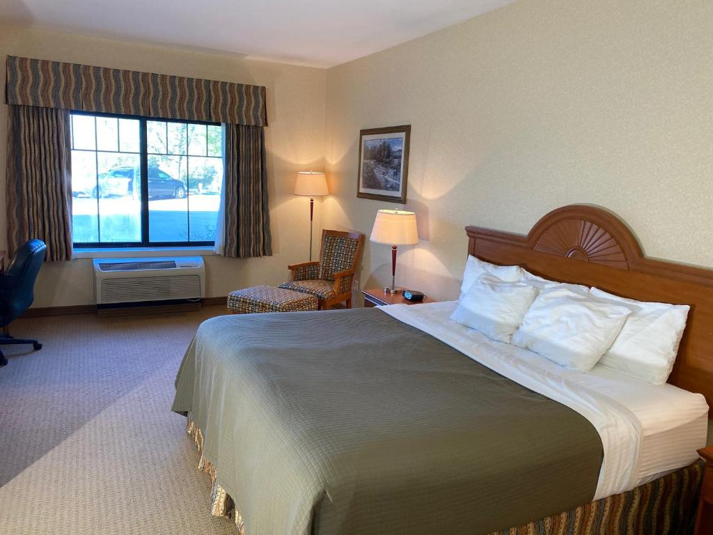 A bed or beds in a room at Red Coach Inn & Suites