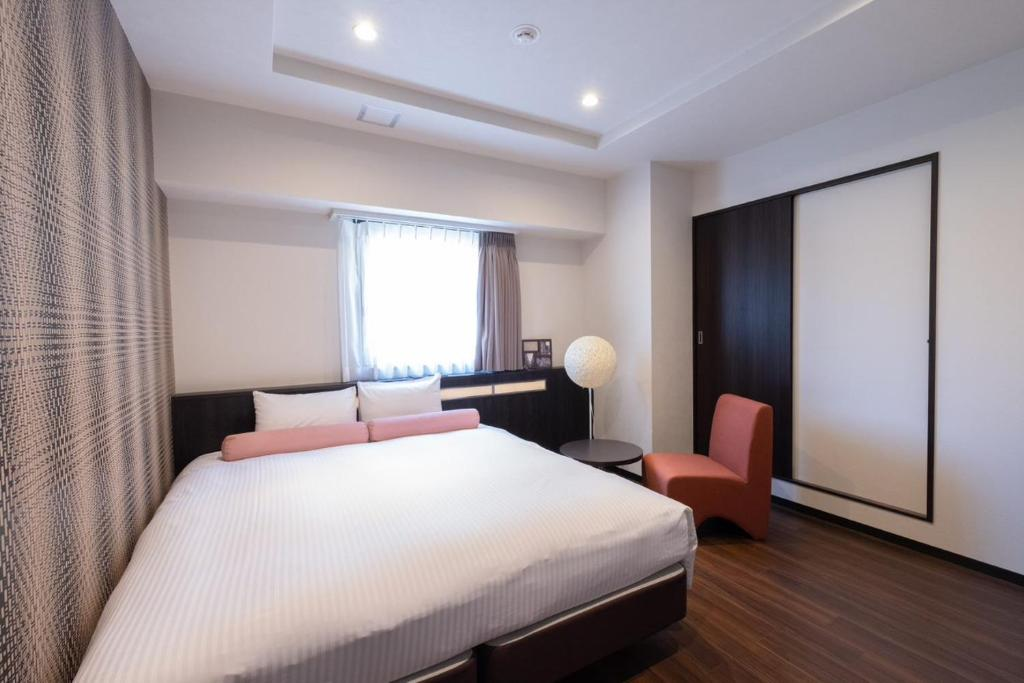 A bed or beds in a room at Nipponbashi Luxe Hotel