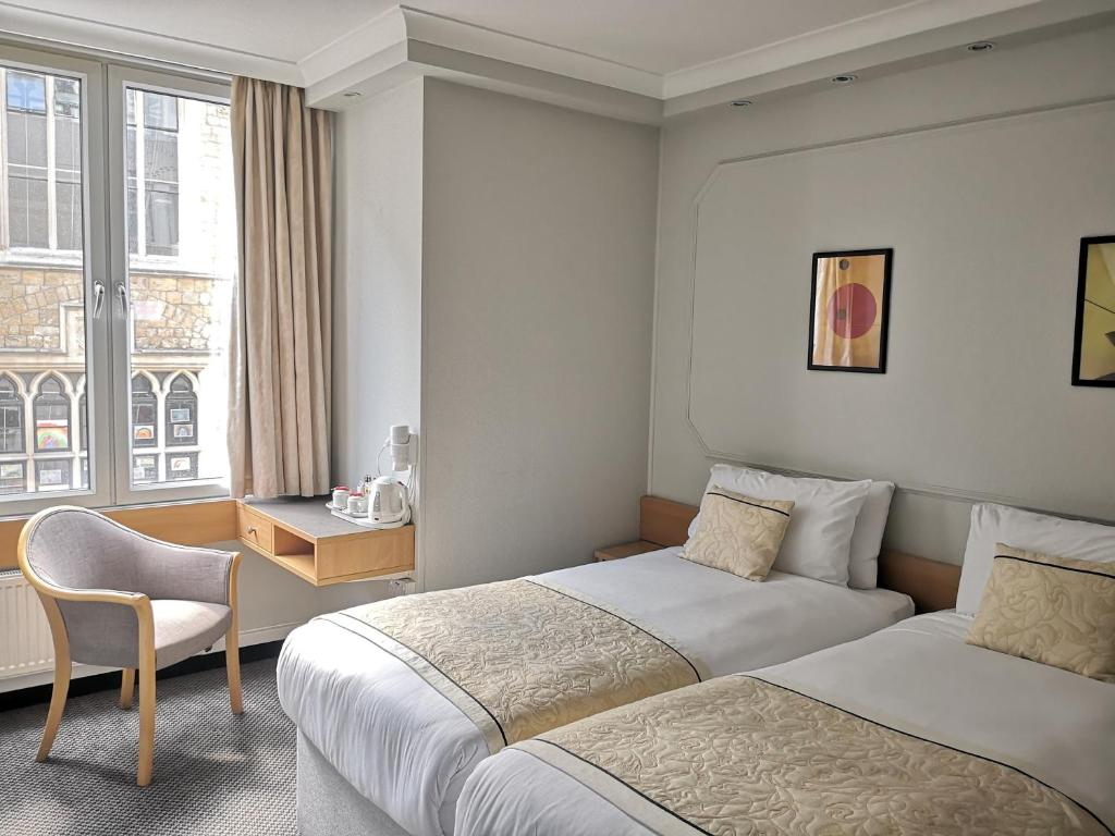 A bed or beds in a room at Lancaster Hall Hotel