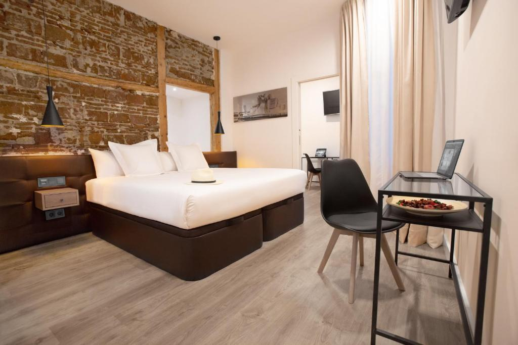 A bed or beds in a room at Woohoo Rooms Fuencarral