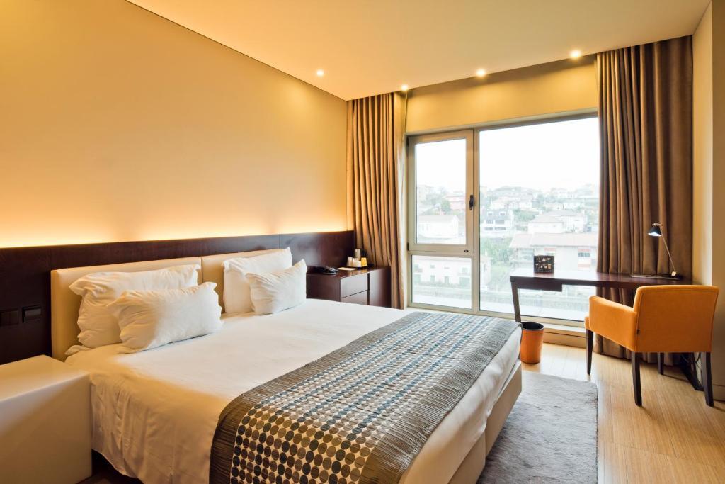 A bed or beds in a room at Golden Tulip São João da Madeira Hotel
