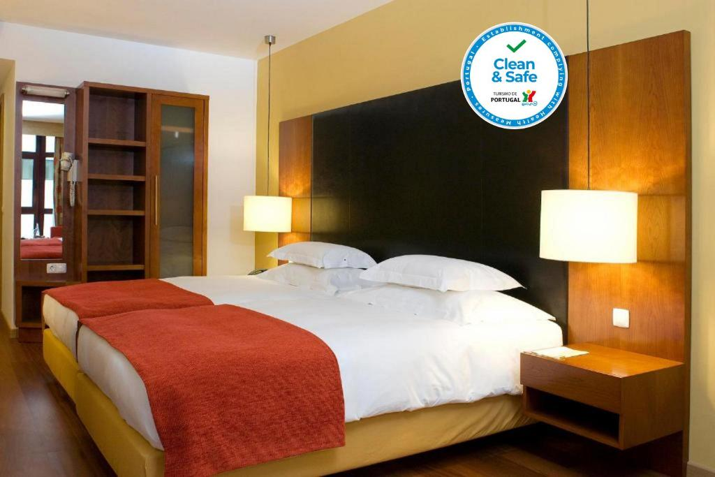 A bed or beds in a room at Leziria Parque Hotel