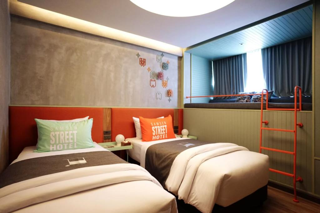 A bed or beds in a room at Samsen Street Hotel
