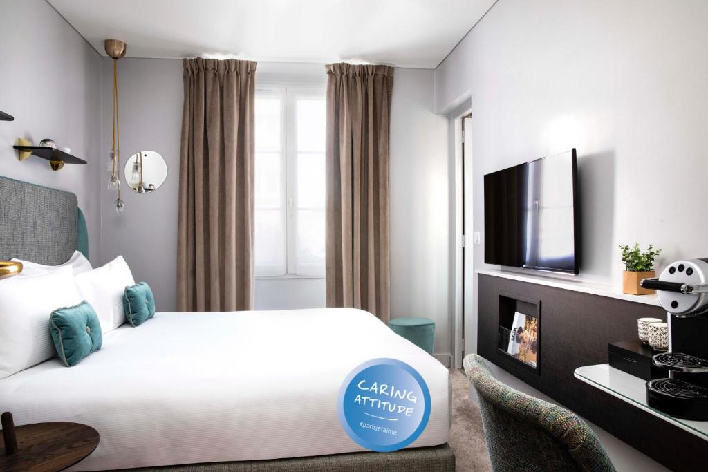 A bed or beds in a room at Hôtel Eiffel Saint Charles